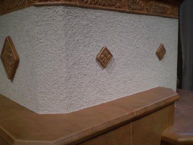 Оштукатуренную печь можно украсит несложными орнаментами или декоративными плитками