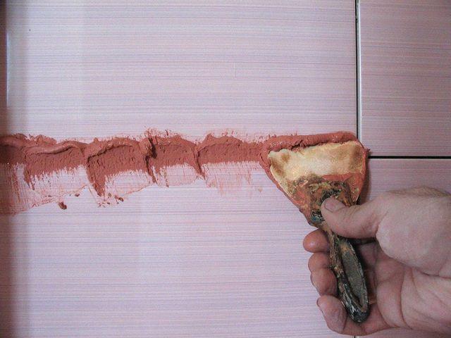 Затирка швов с использованием резинового шпателя