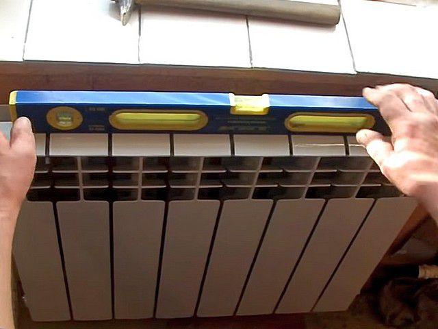 Положение радиатора контролируют уровнем – в горизонтальной и вертикальной плоскости, а также добиваются равного расстояния с обеих сторон от стены
