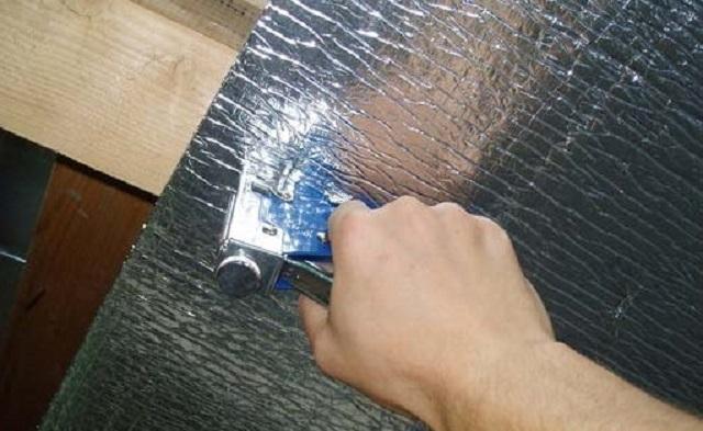 Утепление потолка. Закрепление полотен к обрешетке производится с помощью скоб.