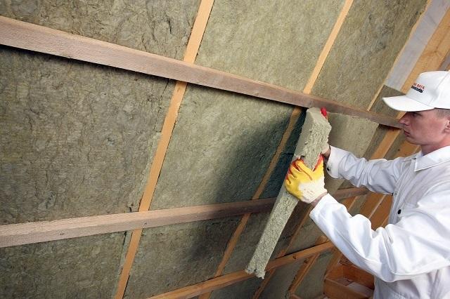 Монтаж плит из базальтовой ваты между направляющими деревянной обрешетки при утеплении частного дома изнутри.