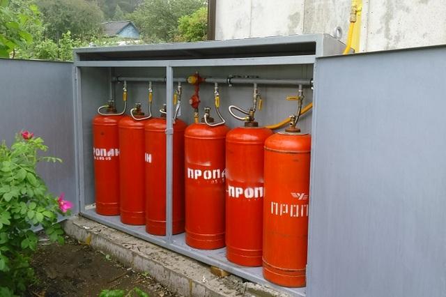 Вынесенный на улицу шкаф с коллектором, к которому подключено шесть газовых баллонов