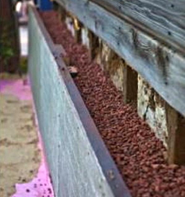 Цоколь деревянного дома, утепленный и защищенный от проникновения грызунов керамзитом.