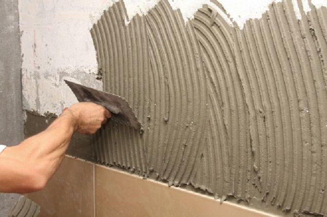 Нанесение и распределение клея на поверхности стены печки
