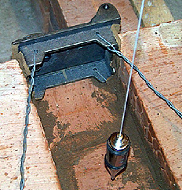Установка чугунных дверец с фиксацией проволоки между кирпичами кладки