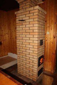 Узкая высокая отопительная печь способна обогреть две соседние комнаты