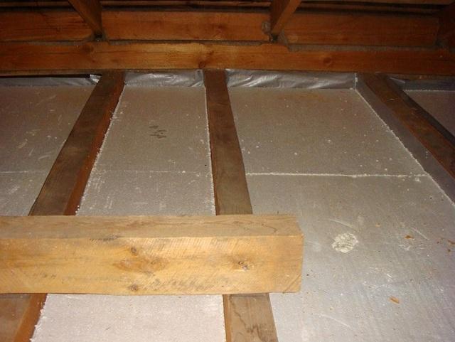 Утепление перекрытия пенопластом. Материал должен максимально плотно входить между деревянными балками или лагами.